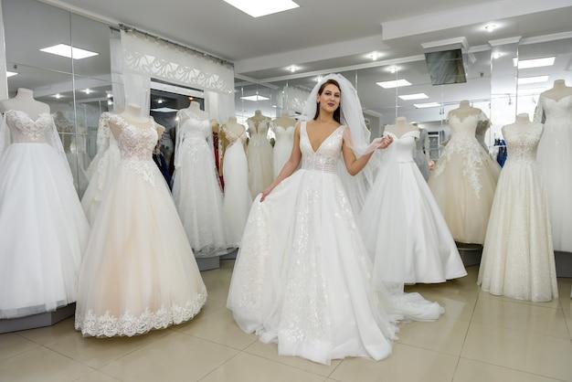 Aantrekkelijke jonge vrouw die trouwjurk draagt in bruidswinkel