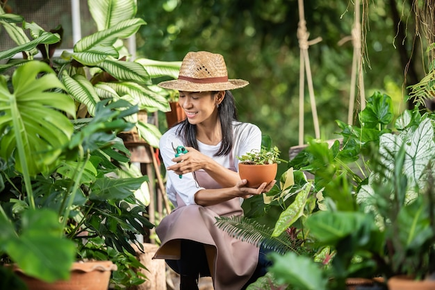 Aantrekkelijke jonge vrouw die werkt met decoratieve planten in tuincentrum. vrouwelijke supervisor die planten onderzoekt in tuinieren buiten in de zomerse natuur. mooie tuinman glimlachen. planten verzorging.