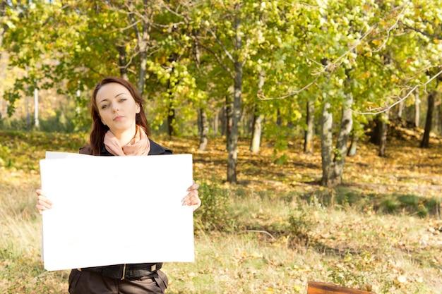 Aantrekkelijke jonge vrouw die zich in bosrijk landschap bevindt dat een lege witte kaart houdt