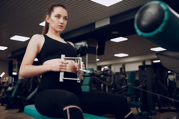 Aantrekkelijke jonge vrouw doet oefeningen voor armen en rug in een sportschool