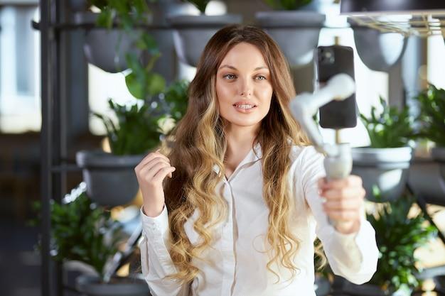Aantrekkelijke jonge vrouw doet selfie in café
