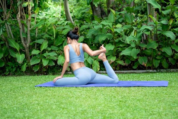 Aantrekkelijke jonge vrouw doet yoga in een elegante houding, in het groene park