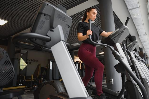 Aantrekkelijke jonge vrouw draait op een loopband, houdt zich bezig met fitness sportclub