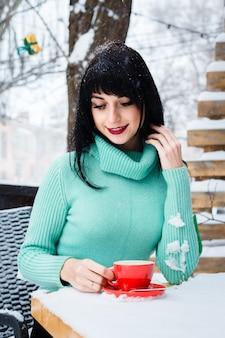 Aantrekkelijke jonge vrouw drinkt een kopje koffie in het straatcafé op een besneeuwde winterdag