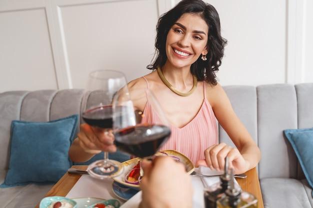Aantrekkelijke jonge vrouw en man rammelende glazen alcoholische drank in restaurant