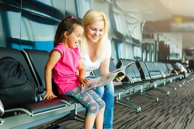 Aantrekkelijke jonge vrouw en schattige kleine dochter zijn klaar voor reizen