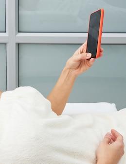 Aantrekkelijke jonge vrouw gebruikend een smartphone en texting terwijl het opleggen van een massagebed in een kuuroord