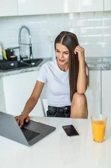 Aantrekkelijke jonge vrouw gebruikend laptop en zittend in de keuken