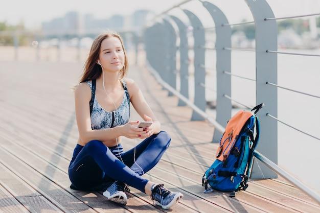 Aantrekkelijke jonge vrouw geniet van rustige sfeer in stedelijk gebied, ademt frisse lucht, zit gekruiste benen, luistert muziek