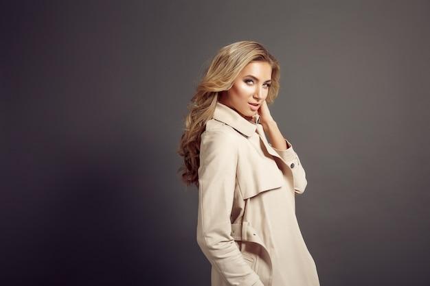 Aantrekkelijke jonge vrouw in beige jas