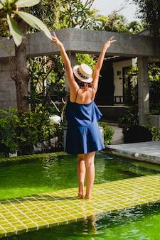 Aantrekkelijke jonge vrouw in blauwe jurk en strooien hoed bij het zwembad