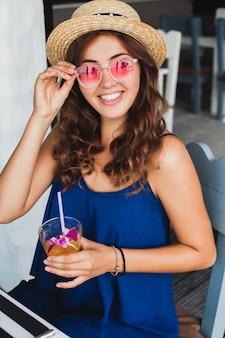 Aantrekkelijke jonge vrouw in blauwe jurk en strooien hoed roze zonnebril dragen, alcohol cocktail drinken op tropische vakantie en zittend aan tafel in de bar