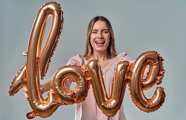 Aantrekkelijke jonge vrouw in blouse staat met luchtballon met het label liefde in handen op grijs.
