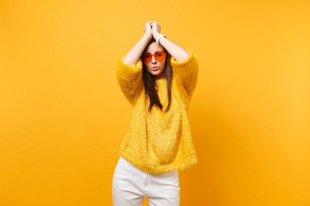 Aantrekkelijke jonge vrouw in bont trui, witte broek en hart oranje bril handen op het hoofd geïsoleerd op heldere gele achtergrond. mensen oprechte emoties, lifestyle concept. reclame gebied.