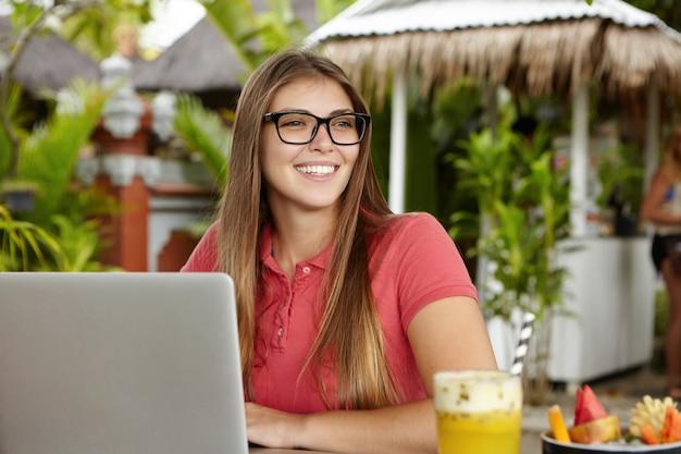 Aantrekkelijke jonge vrouw in bril op zoek vrolijk tijdens het voeren van videogesprek met haar vriend