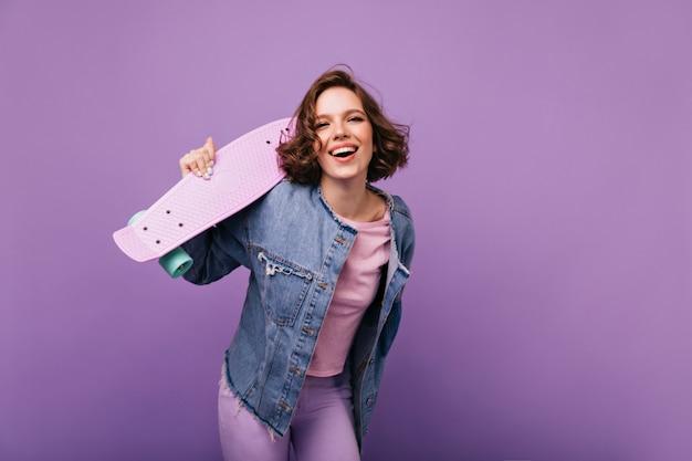Aantrekkelijke jonge vrouw in casual kleding glimlachen. mooi europees meisje met skateboard plezier.