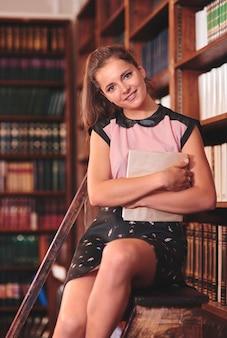 Aantrekkelijke jonge vrouw in de bibliotheek die direct kijkt