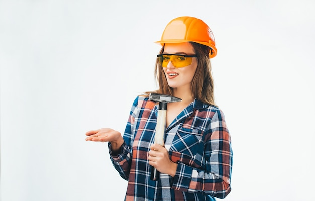 Aantrekkelijke jonge vrouw in de bouw van helm met hamer en oranje beschermende bril op wit