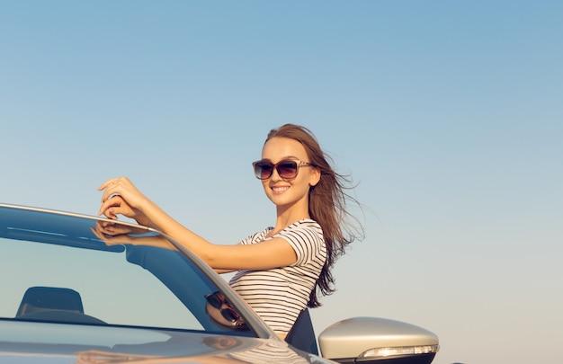Aantrekkelijke jonge vrouw in de buurt van een converteerbare auto