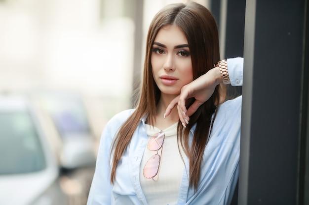 Aantrekkelijke jonge vrouw in een manierschot. mooi modieus jong meisje dat op weg ontwaakt. elegante brunette met lang haar en lang haar.