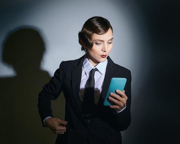 Aantrekkelijke jonge vrouw in een mannenkostuum houdt een smartphone in haar handen