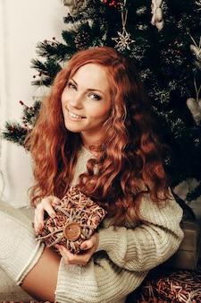 Aantrekkelijke jonge vrouw in een schot van de de wintermanier die een witte wollen sweater en gebreide sokken draagt. kerstmis.