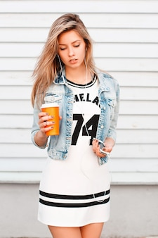 Aantrekkelijke jonge vrouw in een trendy denim jasje in een sportieve stijlvolle jurk met witte koptelefoon in haar oren staat in de buurt van een houten muur. sexy meisje drinkt warme koffie en luistert naar muziek.