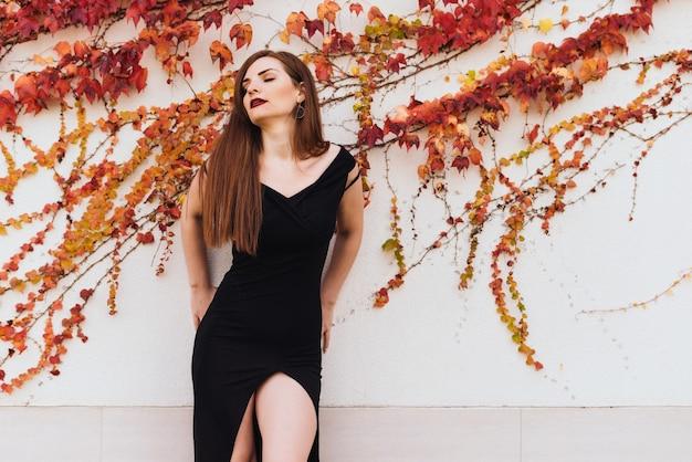 Aantrekkelijke jonge vrouw in een zwarte mooie jurk poseren tegen een ongewone muur achtergrond, ogen dicht