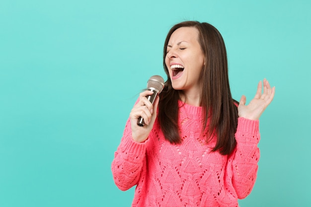 Aantrekkelijke jonge vrouw in gebreide roze trui met gesloten ogen in de hand houden, zingen lied in microfoon geïsoleerd op blauwe muur achtergrond, studio portret. mensen levensstijl concept. bespotten kopie ruimte.