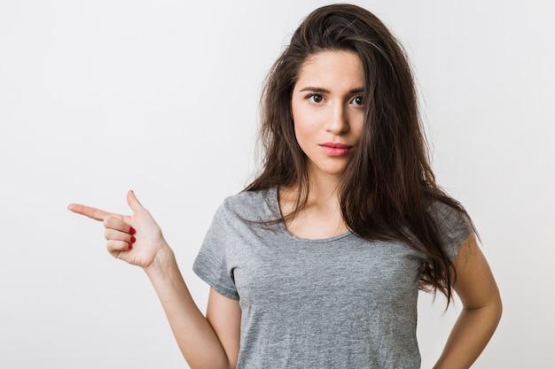 Aantrekkelijke jonge vrouw in grijze t-shirt wijzende vinger, gebaren