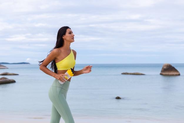 Aantrekkelijke jonge vrouw in kleurrijke sportslijtage op strand