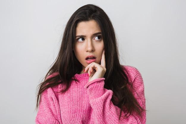 Aantrekkelijke jonge vrouw in roze trui, verbaasde gezichtsuitdrukking, open mond, denken, geïsoleerd, close-up portret