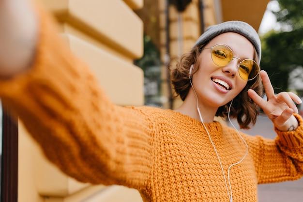 Aantrekkelijke jonge vrouw in sport hoed selfie met vredesteken maken tijdens wandeling buiten in koude dag