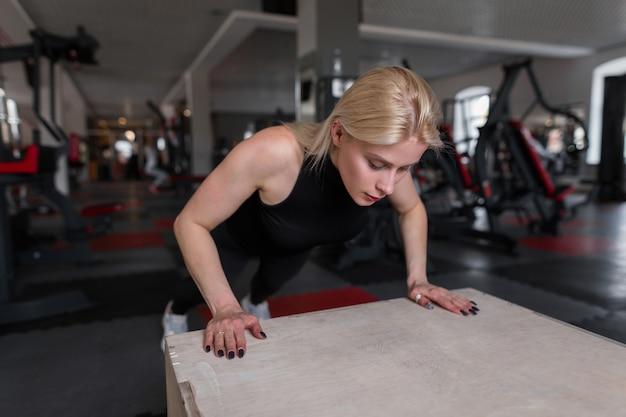 Aantrekkelijke jonge vrouw in sportkleding doet push-ups in een fitness-studio