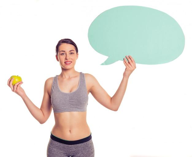Aantrekkelijke jonge vrouw in sportkleding lacht.
