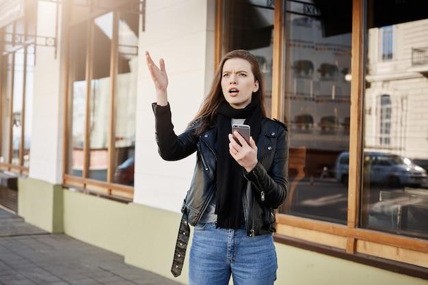 Aantrekkelijke jonge vrouw in trendy leerlaag die met opzij palm wijzen terwijl omhoog het kijken en het houden van smartphone