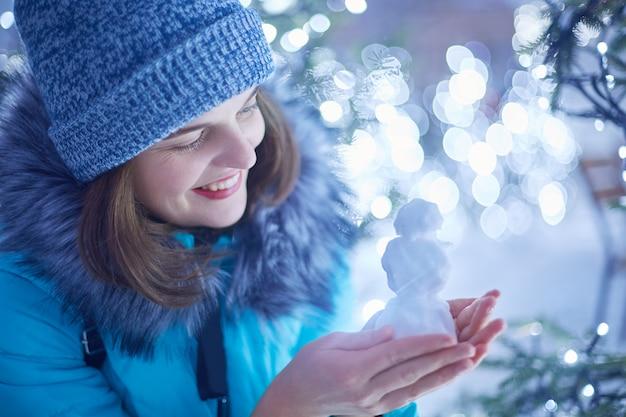 Aantrekkelijke jonge vrouw in winterkleren modellen figuur uit sneeuw, in een goed humeur als wandelingen tijdens ijzig winterweer