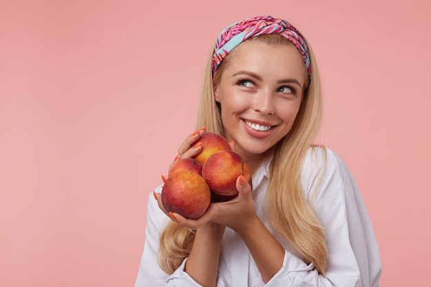Aantrekkelijke jonge vrouw in wit overhemd en gekleurde hoofdband met lang blond haar die vreugdevol opzij kijken, perziken in handen houden