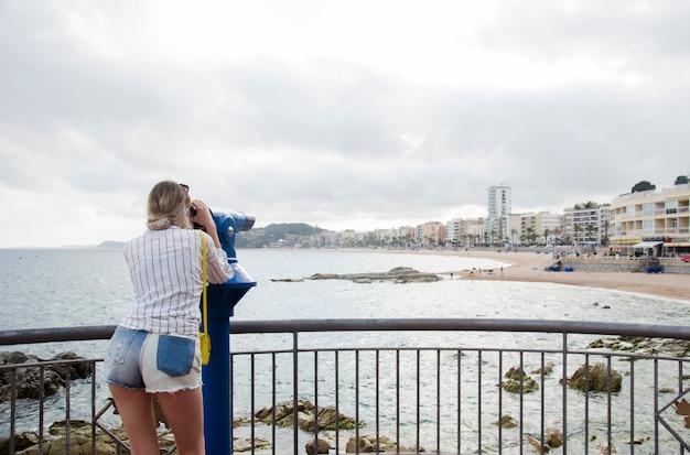 Aantrekkelijke jonge vrouw in wit overhemd en met een geel zakje op zoek op een zee in een zonnige dag in verrekijker op een strand van lloret de mar, costa brava, spanje. vrouw kijken in toeristische telescoop.