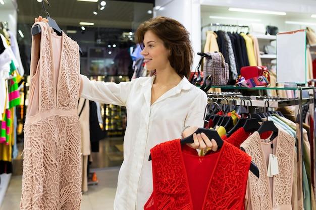 Aantrekkelijke jonge vrouw kiest jurk voor een date staande tussen kledingrekken met lichtroze jurk in de ene hand en baggerjurk in de andere.