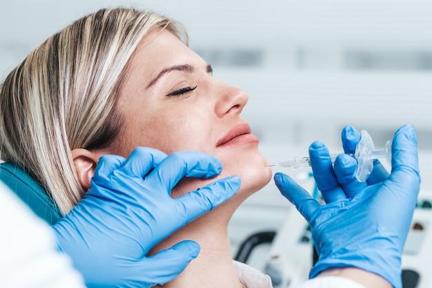 Aantrekkelijke jonge vrouw krijgt een verjongende gezichtsinjecties. de deskundige schoonheidsspecialiste vult vrouwelijke rimpels op met hyaluronzuur.