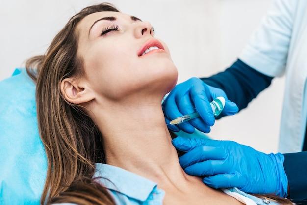 Aantrekkelijke jonge vrouw krijgt een verjongende gezichtsinjecties. ze zit rustig in de kliniek. de deskundige schoonheidsspecialiste vult vrouwelijke rimpels op met hyaluronzuur.