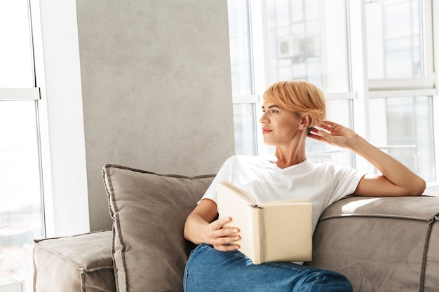 Aantrekkelijke jonge vrouw leesboek zittend op een bank thuis