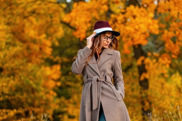 Aantrekkelijke jonge vrouw mannequin met krullend haar in een elegante hoed in een stijlvolle jas in trendy bril geniet van de rest in het herfstpark. vrij modieus meisje hipster is ontspant buitenshuis.