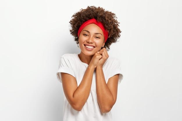 Aantrekkelijke jonge vrouw met afro kapsel, handen tegen elkaar gedrukt houdt, draagt rode hoofdband, casual kleding