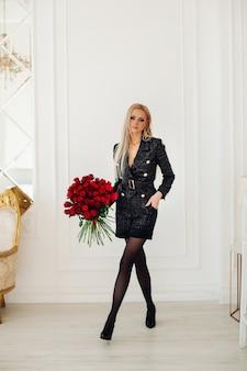 Aantrekkelijke jonge vrouw met blond haar in stijlvolle zwarte jurk houdt een boeket rode rozen in luxe appartementen