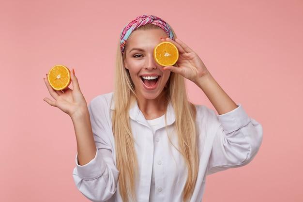 Aantrekkelijke jonge vrouw met brede charmante glimlach die pret maakt, gesneden sinaasappel dichtbij haar oog houdt