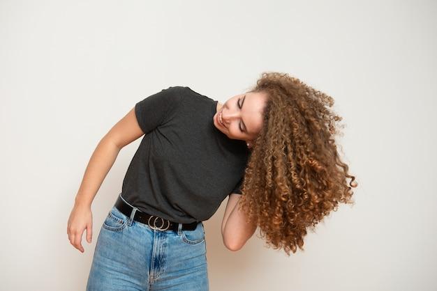 Aantrekkelijke jonge vrouw met bruin krullend kapsel op witte achtergrond