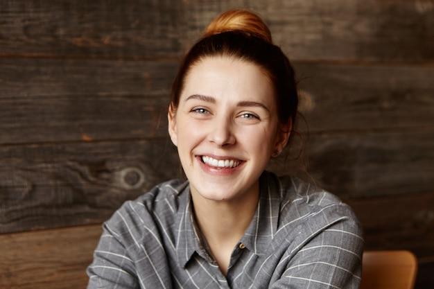 Aantrekkelijke jonge vrouw met charmante glimlach die gelukkig en vrij voelt na het afstuderen van universiteit, ontspannend bij koffie, wachtend op voedsel en het maken van plannen voor de toekomst. gembervrouw die rust hebben binnen