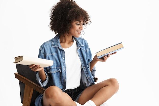Aantrekkelijke jonge vrouw met denim zittend in een stoel geïsoleerd over een witte muur, een boek kiezend